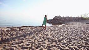 Gesamtplan Ein herrliches Mädchen geht entlang die Küste und der Aufstellung stock video