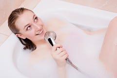 Gesangbadekurort: unter Verwendung der Dusche als attraktive glückliche lächelnde schöne junge Frau des blonden Mädchens des Mikr Stockbilder