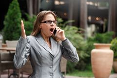 Geschäftsfrau in den Brillen, die auf der Stadtstraße hat Gespräch auf den Smartphonehänden oben entsetzt stehen stockfotos