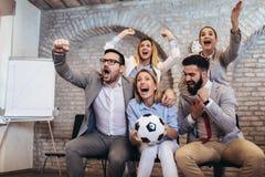 Geschäftsleute oder Fußballfane, die Fußball im Fernsehen aufpassen und Sieg feiern Freundschaft, Sport und Unterhaltungskonzept lizenzfreie stockbilder