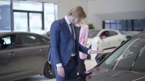 Geschäftsmann, der oben das Auto im Verkaufsstelleabschluß wählt Großer Mann steht nahe Automobil im Automobilausstellungsraum un stock footage
