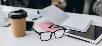 Geschäftsschreibtisch mit einem Notizbuch, Gläsern, Stift und Tablette auf weißer Tabelle lizenzfreie stockbilder