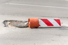 Geschädigte Straßenrekonstruktion oder rote und weiße Zeichenabdeckung der Baubarrikadenvorsicht das offene Loch des Einsteigeloc Lizenzfreies Stockbild