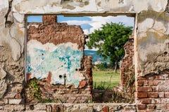 Geschädigter Wand- und Fensterrahmen mit Ansicht zum Ruinenraum und zum grünen Feld des Grases stockfotografie