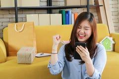 Geschäft beginnen oben asiatische Frau ist glücklich mit ihrer on-line-Bestellung vom Smartphone lizenzfreie stockfotografie