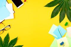 Geschäft flatlay mit tropischen Blättern und Geschäftszubehör: Notizbuch, Klipp, Smartphone, Gläser usw. Draufsicht, gelbes backg lizenzfreie stockfotografie