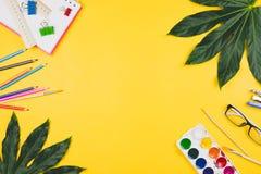 Geschäft flatlay mit tropischen Blättern und Geschäft und künstlerisches Zubehör Stockfotografie