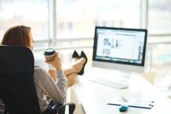 Geschäft Geschäftsfrau mit dem roten Haar sitzt am Tisch in einem Bi lizenzfreie stockfotos