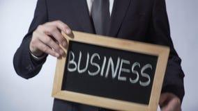 Geschäft geschrieben auf Tafel, Mann in der Klage, die Zeichen, Führung, Ziele hält stock footage