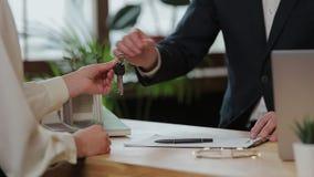 Geschäft, Immobilien, Abkommen und Leutekonzept - bemannen Sie das Geben der Frau von Hausschlüsseln im Büro stock video