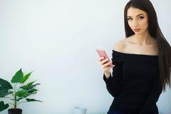Geschäft Junge Geschäftsfrau-Holding in den Händen rufen an Sitzt auf dem Schreibtisch im großen hellen Büro und den Arbeiten übe lizenzfreies stockfoto