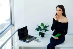 Geschäft Junge Geschäftsfrau-Holding in den Händen rufen an Sitzt auf dem Schreibtisch im großen hellen Büro und den Arbeiten übe lizenzfreies stockbild
