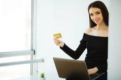 Geschäft Junge Geschäftsfrau-Holding-Kreditkarte in den Händen Sitzt auf dem Tisch bei dem großen hellen Büro und den Arbeiten au lizenzfreie stockbilder