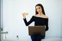 Geschäft Junge Geschäftsfrau-Holding-Kreditkarte in den Händen Sitzt auf dem Tisch bei dem großen hellen Büro und den Arbeiten au stockfotos