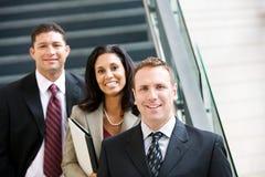 Geschäft: Lächelnder Team Stands Together By Stairs Stockfoto