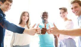 Geschäft, Start und Bürokonzept - glückliches kreatives Team, das Daumen oben im Büro zeigt lizenzfreie stockbilder