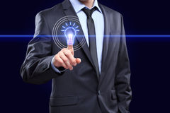 Geschäft, Technologiekonzept - Geschäftsmann, der Knopf mit Birne auf virtuellen Schirmen bedrängt Lizenzfreie Stockbilder