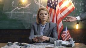 Geschäft und Finanzierung, Glück oder Vermögen und Leutekonzept - Frau über Hintergrund der amerikanischen Flagge gibt Dollargeld stock footage