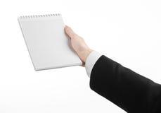 Geschäft und Reporterthema: die Hand eines Journalisten in einem schwarzen Anzug, der ein Notizbuch mit einem Bleistift auf einem Stockfotos
