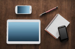 Geschäfts-Arbeit mit einem Tablet, 2 Smartphones und Notizblock Stockfotografie