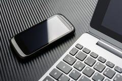 Geschäfts-Arbeit mit schwarzem Smartphone mit der Reflexion, die nach links zu einer Notizbuch-Tastatur, alle über einer Kohlenst Lizenzfreies Stockfoto