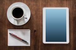 Geschäfts-Arbeit mit Tablet, Kaffee und Notizblock Stockfotos