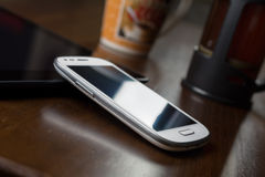 Geschäfts-Arbeit mit Tablet, Smartphone, Kaffee u. Kaffeeproduzenten Stockfoto