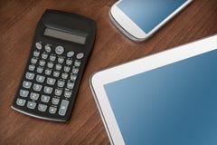 Geschäfts-Arbeit mit Tablet, Smartphone u. Taschenrechner Stockfotos
