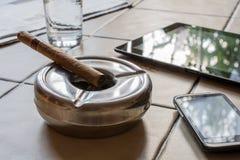 Geschäfts-Arbeit mit Zigarre, Tablet und Smartphone Lizenzfreie Stockfotografie