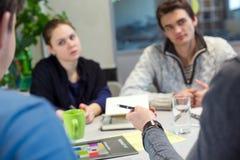 Geschäfts-Diskussions-junge Leute in der Freizeitbekleidung bemannen das Zeigen stockfotografie