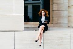 Geschäfts-, Karriere- und Erfolgskonzept Elegante dünne junge Geschäftsfrau, die schwarzen Anzug und Stöckelschuhe, sitzendes gek stockfotografie