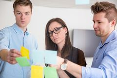 Geschäfts-Kollegen, die über den klebenden Anmerkungen fest auf Glas sich besprechen lizenzfreie stockbilder