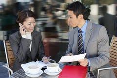 Geschäfts-Kollegen, die Dokumente bei Café im Freien wiederholen Stockfoto