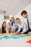 Geschäfts-Kollegen, die mit Aufklebern gedanklich lösen Lizenzfreie Stockfotos