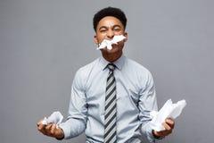 Geschäfts-Konzept - junger verärgerter Afroamerikanergeschäftsmann beim Essen des balled Berichtspapiers Erfolgloses Projekt Stockbilder