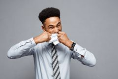 Geschäfts-Konzept - junger verärgerter Afroamerikanergeschäftsmann beim Essen des balled Berichtspapiers Erfolgloses Projekt Stockbild