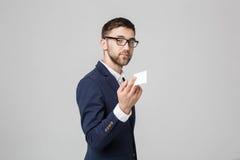 Geschäfts-Konzept - Porträt-hübscher Geschäftsmann, der Namenkarte mit lächelndem überzeugtem Gesicht zeigt Weißer Hintergrund Ko Lizenzfreie Stockfotografie