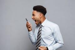 Geschäfts-Konzept - stressiger Afroamerikanergeschäftsmann, der am Handy schreit und schreit Lizenzfreie Stockfotos