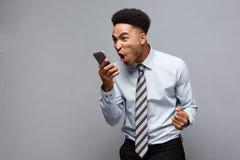 Geschäfts-Konzept - stressiger Afroamerikanergeschäftsmann, der am Handy schreit und schreit Stockbild