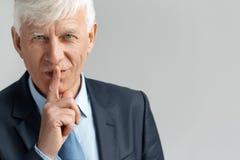 Geschäfts-Lebensstil Geschäftsmannstellung auf der grauen darstellenden geheimen Geste, die Kamera spielerische Nahaufnahme schau stockfotografie