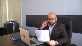 Geschäfts-, Leute-, Schreibarbeits- und Technologiekonzept - Geschäftsmann mit der Laptop-Computer und Papieren, die im Büro arbe stock video footage