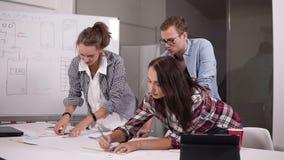 Geschäfts-, Leute- und Teamwork-Konzept - lächelndes junges Geschäftsteam mit den Papieren, die im Büro sich treffen, machen Kenn stock video footage