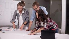 Geschäfts-, Leute- und Teamwork-Konzept - lächelndes junges Geschäftsteam mit den Papieren, die im Büro sich treffen, machen Kenn stock video