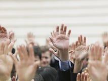 Geschäfts-Menge, die Hände anhebt Stockfoto