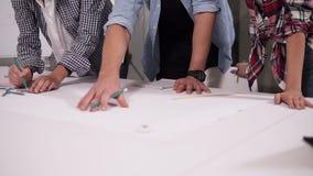 Geschäfts- oder Bildungs-, Leute- und Teamwork-Konzept - kaukasisches junges Team mit den Papieren, die im Büro sich treffen, mac stock footage