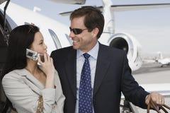 Geschäfts-Paare, die Flugplatz sich betrachten Stockfoto