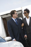 Geschäfts-Paare, die zusammen am Flugplatz stehen Lizenzfreie Stockbilder
