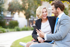 Geschäfts-Paare unter Verwendung Digital-Tablets auf Park-Bank Lizenzfreies Stockbild