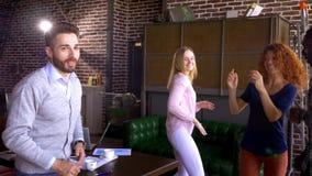 Geschäfts-, Start- und Leutekonzept - glückliches kreatives Team mit Computern und Ordner, die Projekt im Dachboden geteilt bespr stock video footage
