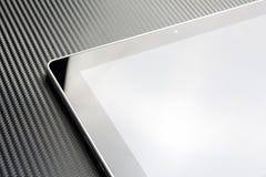 Geschäfts-Tablet mit leerem Bildschirm und Reflexion auf Kohlenstoff-Hintergrund Lizenzfreie Stockfotos